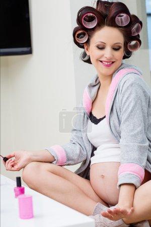 Photo pour Femme enceinte avec des rouleaux de cheveux ongles traitement - image libre de droit