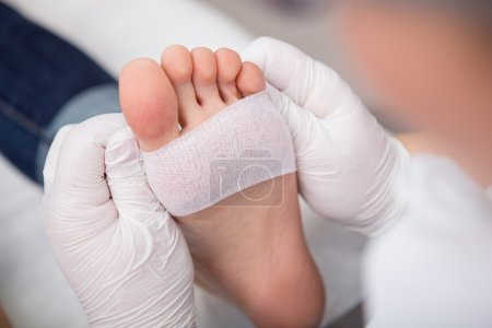 podiatrist ( chiropodist ) cleaning womans feet ( toenails )