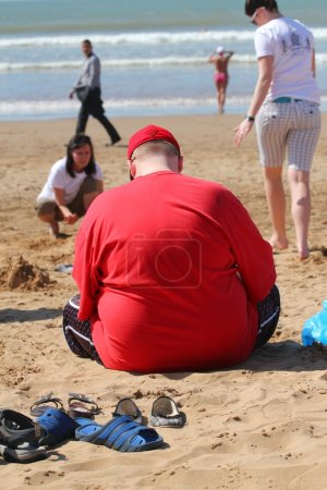 Photo for Obese fat man sitting on the beach in Agadir, Morocco - Royalty Free Image
