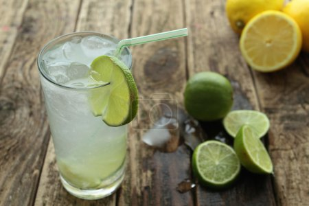 Photo for Cold lemon drink with ice and lime on a wooden table - Royalty Free Image
