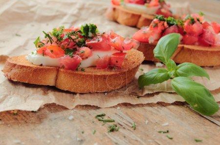 Photo for Bruschetta with tomato, garlic and mozzarella with fresh basil - Royalty Free Image