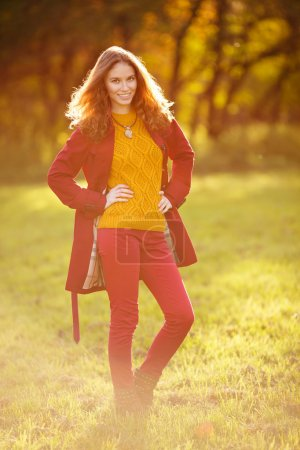 Photo for Outdoor portrait of beautiful redhead woman in red cloak - Royalty Free Image