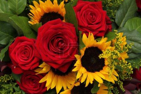rosas rojas y girasoles en un arreglo floral