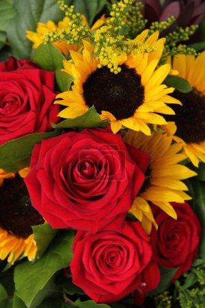 Foto de Grandes rosas rojas y girasoles en un arreglo floral - Imagen libre de derechos