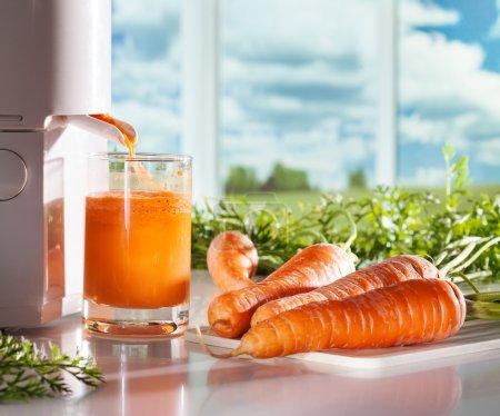 Photo for Fresh carrot juicFresh carrot juice and juicer on window backgrounde - Royalty Free Image