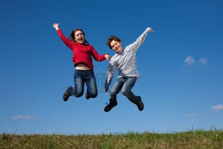 Kids jumping against blue sky