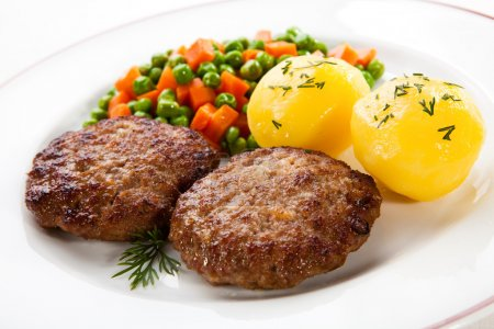 Fried pork chops with boiled potatoes and vegetables