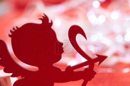 Photo pour Cupidon sur fond rouge - image libre de droit