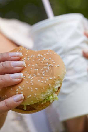 Photo for Woman eating hamburger and cocktail - Royalty Free Image
