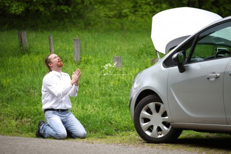 Photo for Funny driver praying a broken car by the road - Royalty Free Image