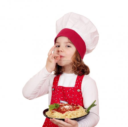 little girl cook holding a plate of spaghetti
