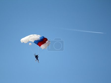 parachutist and airplane on blue sky