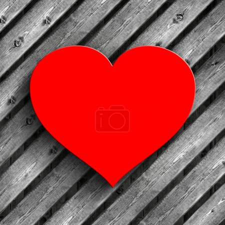 Red heart on wooden planks background