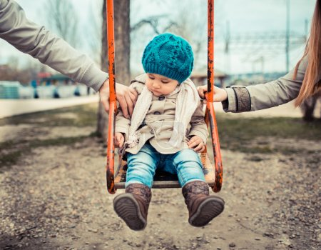 Photo for Sad child on a swing, inbetween her divorced parents holding her separatedly . - Royalty Free Image