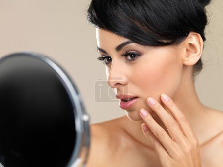 Beautiful woman looking in a hand mirror