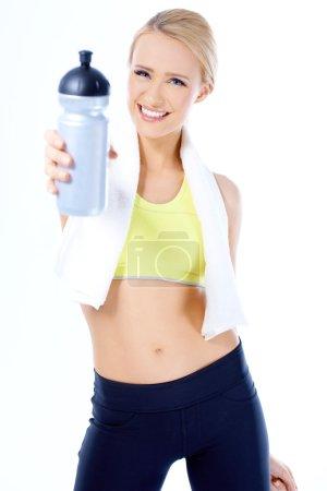 Cute sporty blond woman holding water bottle