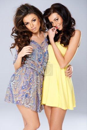 Two seductive coy beautiful young woman