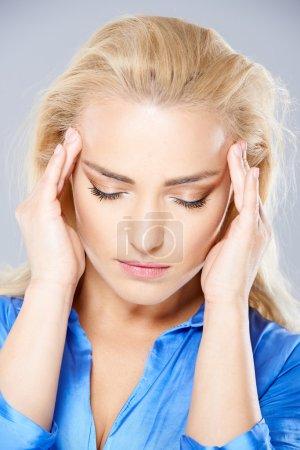 Beautiful young woman suffering from a headache