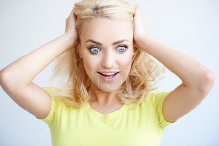 Frustrated young woman with her hands in her hair