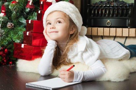 Pretty girl in Santa hat writes letter to Santa