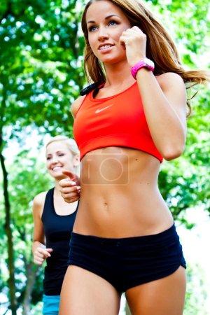 Running in city park. Woman runner outside jogging