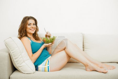 Photo for Young woman with long hair sitting on sofa at home and eating healthy food. - Royalty Free Image