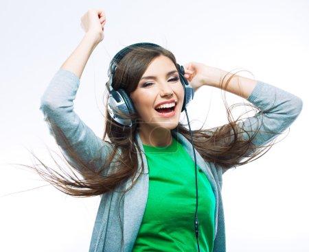 Photo pour Femme avec écouteurs écoutant de la musique. Adolescente dansant sur fond blanc isolé. Concept de style de vie adolescent - image libre de droit