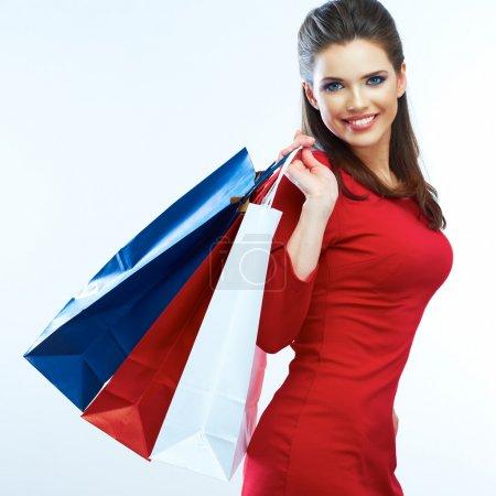 Photo pour Portrait de femme de mode isolé. Fond blanc. Joyeux sac à provisions. Robe rouge. femelle beau modèle . - image libre de droit