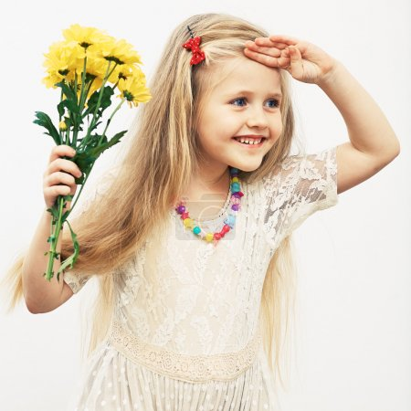 Photo pour Portrait isolé de petite fille tenant des fleurs jaunes - image libre de droit
