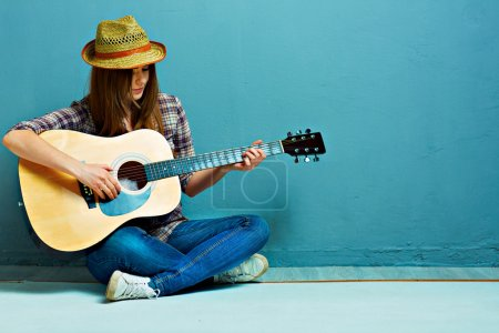 Photo for Country style girl with guitar sitting on floor - Royalty Free Image