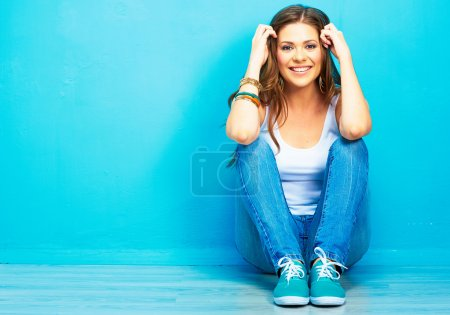 Photo for Young girl sitting on floor against blue background - Royalty Free Image