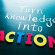 Turn knowledge into action, conceptual words on bl...