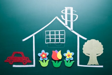 Photo for Wealth concept. Money sign on drawing house on blackboard. Handmade car, tree and flowers as decoration. - Royalty Free Image