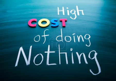 Photo for High cost of doing nothing, conceptual words on blackboard - Royalty Free Image
