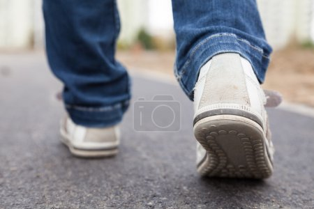 Photo for Teenager walking in sport shoes on pavement in autumn day - Royalty Free Image