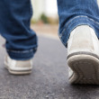 Teenager walking in sport shoes on pavement in aut...