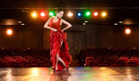 Photo for Sexy flamenco dancer performing her dance in a red long dress. - Royalty Free Image