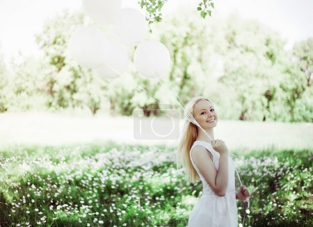 Photo for Happy young woman with white balloons in the summer park - Royalty Free Image
