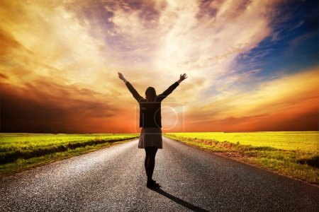 Happy woman standing on long road at sunset