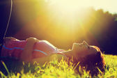 Young pretty woman lying on the grass at summer sunset