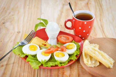 Breakfast with hard boiled eggs, sliced in halves, cup of tea, salad, tomatoes, cheese and bread on the red plate and wooden background