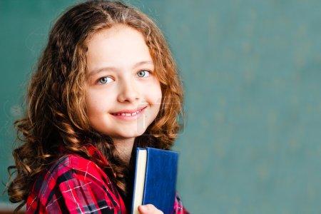 Pretty schoolgirl holding a book