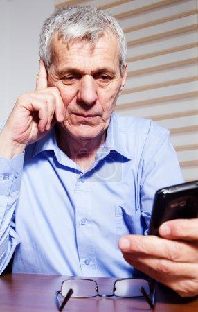 An senior businessman using phone at his office