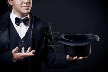 Photo pour Gros plan de magicien montrant des tours avec chapeau haut isolé sur fond sombre - image libre de droit