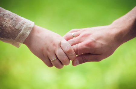 Closeup image of a young couple holding hands, outdoors
