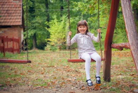 Photo for Happy Little Girl Smiling on Swing - Royalty Free Image