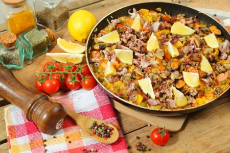 Photo for Paella with seafood on wooden table - Royalty Free Image
