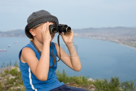 Photo for Boy looking through binoculars from the top of the mountain. In the background of the sea coast. - Royalty Free Image