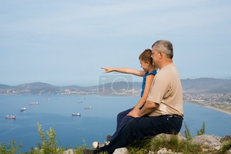 Grandfather and grandson at the top of the mountain.