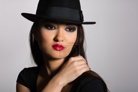 Photo for Beautiful young Asian girl in a black hat. - Royalty Free Image